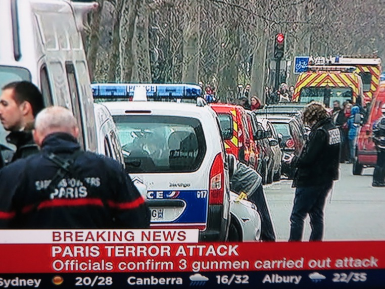 The BBC World Service Announces that the French Police are seeking three suspects in the Charlie Hebdo attack within hours   of the  event. This shot was taken around six hours after the attack.