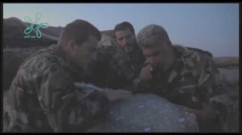 This shot taken from a videocalled entry into Kvrenbaudh appears to show a Russian advisor and two Iranian IRGC members poring over a map f Latakia. The