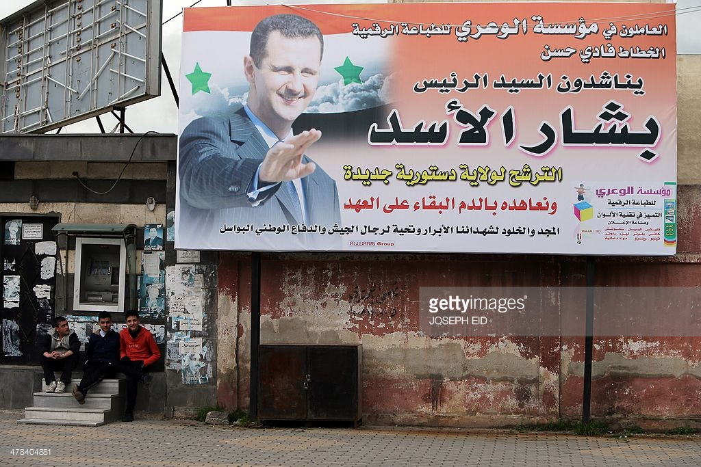A poster of Syrian President Bashar al Assad agaisnt the desolation of war torn Syria. Image belongs to Getty Images.