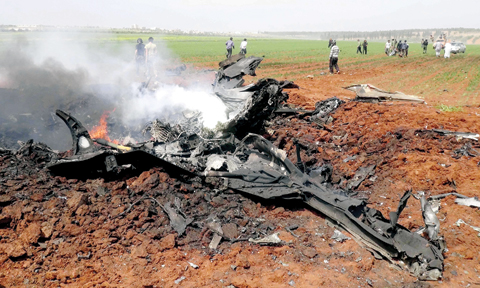 Flattened Su22 lies in the fields of Aleppo yesterday.