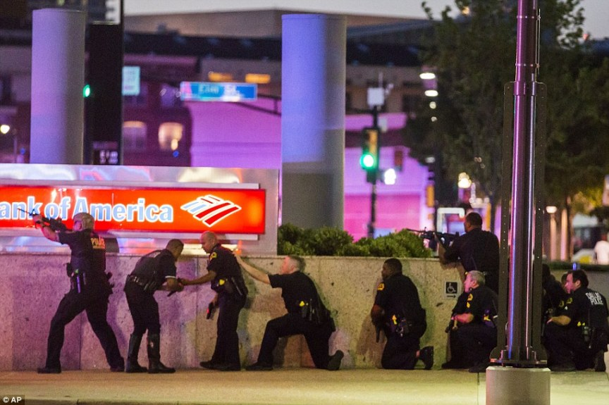 This photograph depicts Dallas police taking cover from the claimed snipers. Is this a realistic defensive cover position against a sniper in an elevated position? Highly reminscient of the ridiculous police response to the Ottawa hoax.