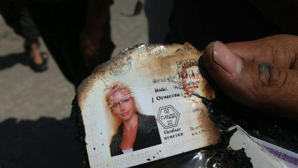 Insurgents diplay an ID card they retriieved from the wreckage of the downed Helicopter.