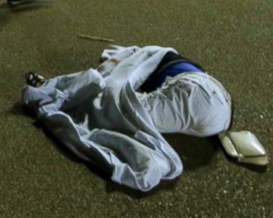 This is supposed to be a dead body. This is a blue circular object wrapped in a sheet.with a purse placed beside it. No body and no blood presented as a dead body makes it perfectly clear the event was completely staged. A real attack would not require blue circular objects wrapped in sheets to be presented as one of the victims.